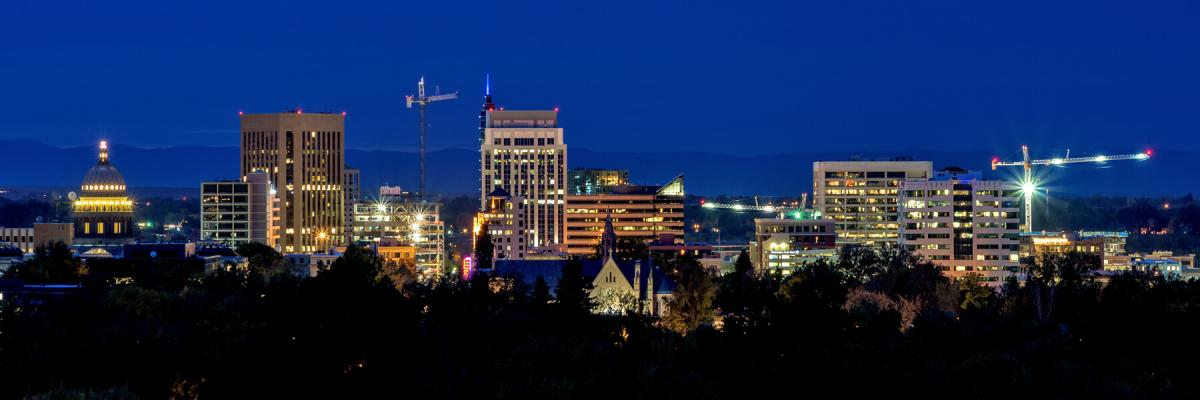 Construction cranes over Boise skyline at night